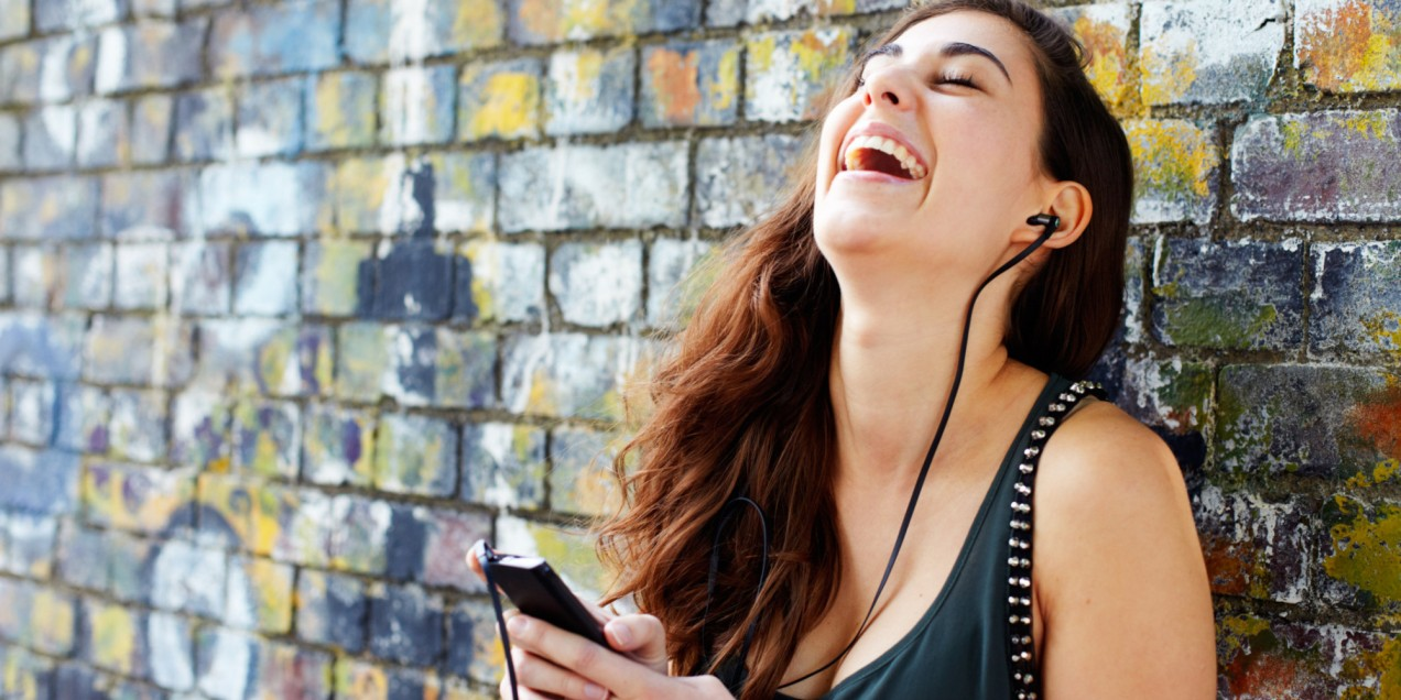Young woman laughing with smart phone + headphones