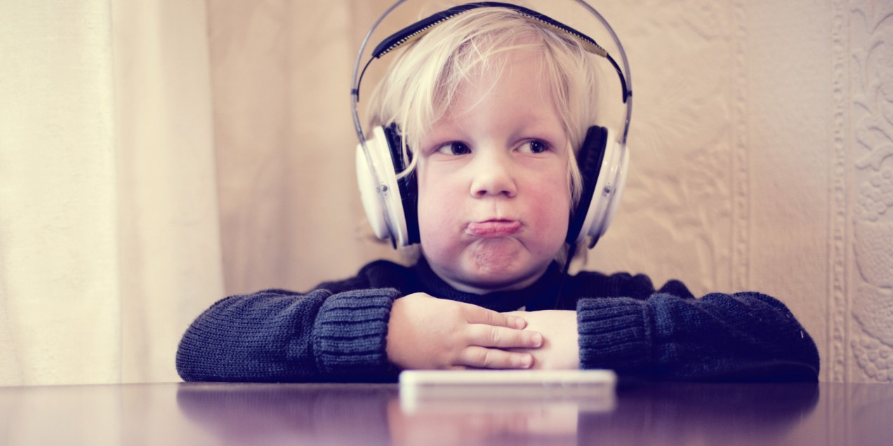 Child with sad face and headphones on